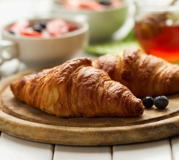 Des délicieux croissants savoureux sur une planche de bois. petit-déjeuner continental traditionnel. granola aux fruits et au miel sur le fond.