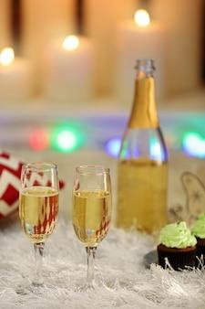 Délicieux cupcakes et champagne sur fond intérieur de maison