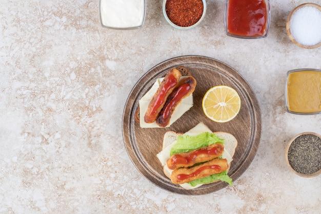 Un délicieux déjeuner servi avec des bâtonnets de poisson et divers assaisonnements et condiments