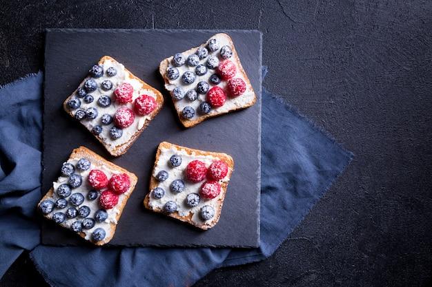 Délicieux dessert aux bleuets et framboises fraîches sur fond noir.