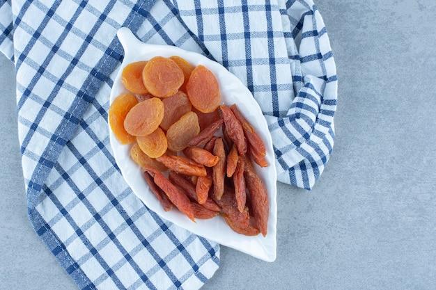Délicieux deux sortes de fruits secs, dans un bol, sur la serviette, sur la table en marbre.