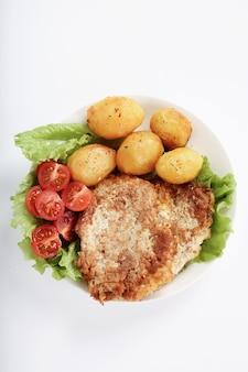 Délicieux dîner avec steaks, pommes de terre bouillies et salade