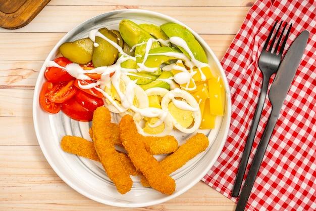 Délicieux doigts de poulet avec une salade d'avocats, tomates cerises, fromage manchego, œuf et concombres aigres avec une vinaigrette alioli. vue aérienne, orientation horizontale.