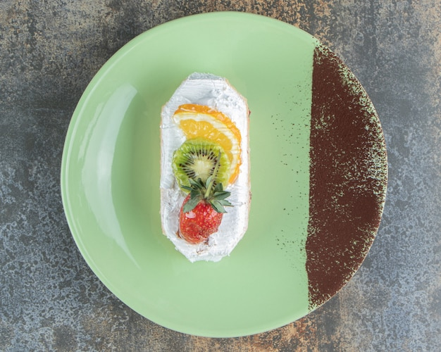 Un délicieux éclair aux fruits sur une assiette verte