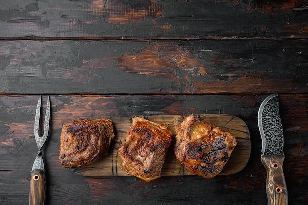 Délicieux ensemble de côtes levées de bœuf braisé, sur fond de table en bois foncé ancien, vue de dessus à plat, avec espace de copie pour le texte