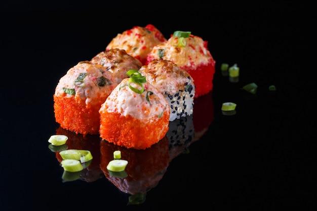 Délicieux ensemble de sushi roll avec du poisson sur un fond noir avec reflet menu et restaurant