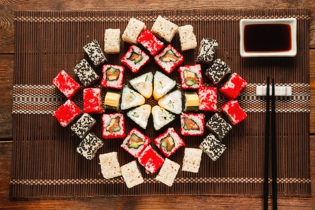 Délicieux ensemble de sushis colorés servis sur un tapis de paille marron, à plat. art culinaire, bel ornement. cuisine japonaise, photo du menu du restaurant.