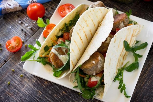 Délicieux enveloppement de tortillas faites maison avec falafel et salade fraîche sur la table tacos végétaliens