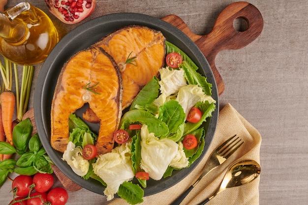 Délicieux filets de saumon cuit. filet de saumon grillé et salade de tomates aux légumes et laitue verte fraîche. concept de nutrition équilibrée pour une alimentation méditerranéenne flexitarienne propre.