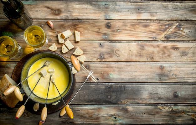 Délicieux fromage à fondue avec tranches de pain et vin blanc.