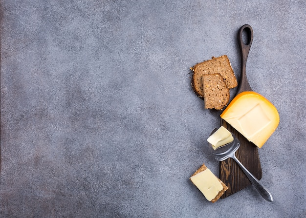 Délicieux fromage gouda hollandais avec tranches de fromage, pain multigrain et couteau spécial