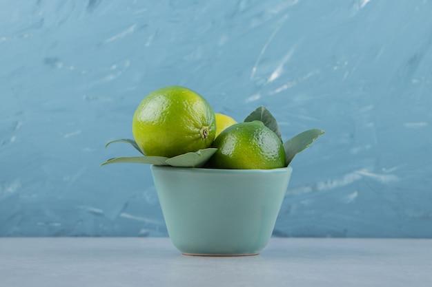 De délicieux fruits de citron vert dans un bol bleu.