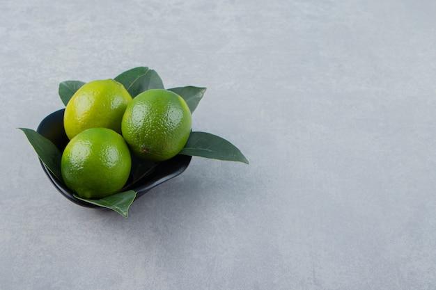 De délicieux fruits de citron vert dans un bol noir.