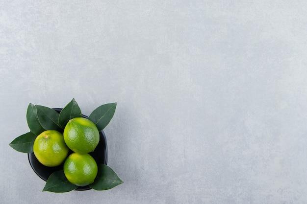 De délicieux fruits de citron vert dans un bol noir