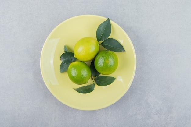 Délicieux fruits de citron vert avec des feuilles sur une plaque jaune