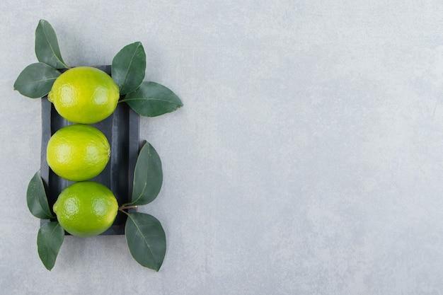Délicieux fruits de citron vert avec des feuilles sur une plaque noire