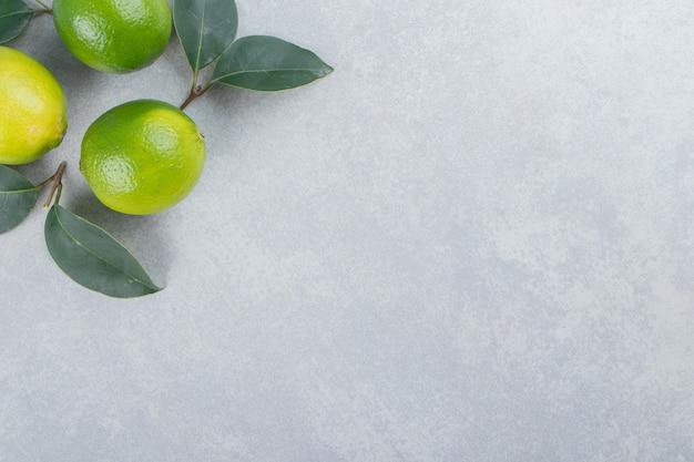 Délicieux fruits de citron vert avec des feuilles sur la surface de la pierre