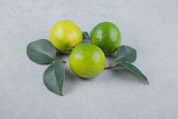 De délicieux fruits de citron vert avec des feuilles sur une table en pierre.