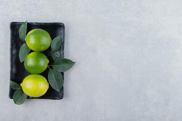 Délicieux fruits de citron vert sur plaque noire.