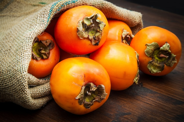 Délicieux fruits frais kaki sur table en bois