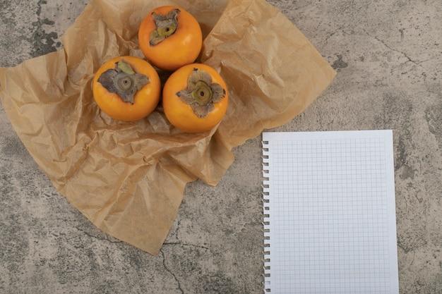 De délicieux fruits fuyu mûrs placés sur une feuille de papier avec du papier vide