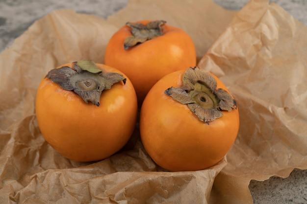De délicieux fruits fuyu mûrs placés sur une feuille de papier