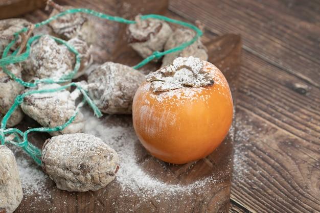Délicieux fruits de kaki frais et séchés sur planche de bois