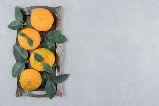 De délicieux fruits de mandarine sur un plateau en métal