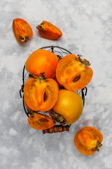Délicieux fruits mûrs de kaki sur béton