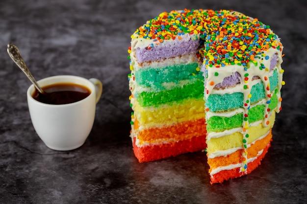 Délicieux gâteau arc-en-ciel fait maison en couches avec une tasse de café.