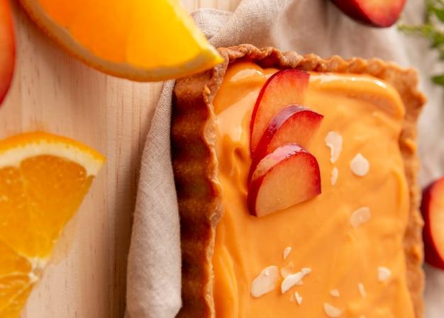 Délicieux gâteau avec arrangement de pêches et d'oranges