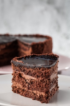 Délicieux gâteau au chocolat sur une plaque sur la table sur fond de marbre. fond d'écran pour pâtisserie ou menu de café. verticale.