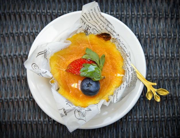Délicieux gâteau au fromage fait maison avec des fruits sur une table en bois blanche.
