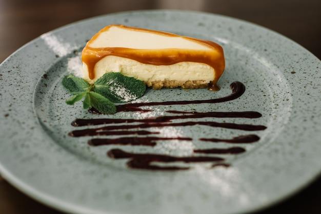 Délicieux gâteau au fromage frais avec du chocolat, du caramel et de la menthe sur la plaque