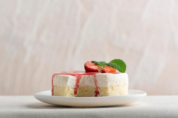 Délicieux gâteau au fromage avec des fraises fraîches et de la menthe sur une plaque blanche