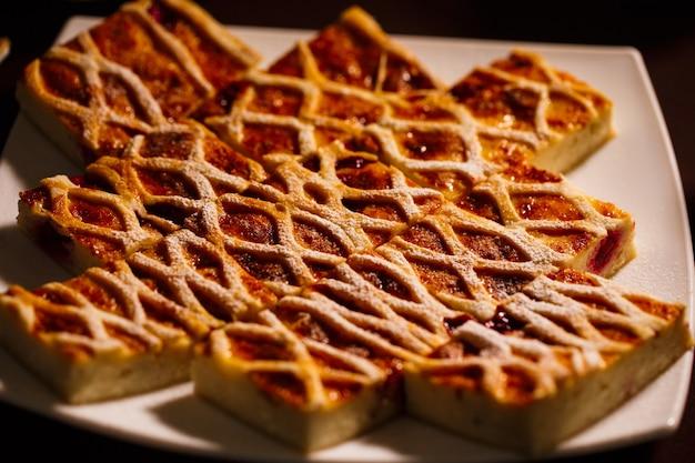 Délicieux gâteau au fromage avec tranche de baies saupoudrée de sucre en poudre sur plaque blanche