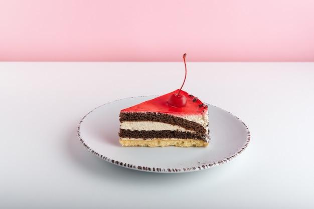 Délicieux gâteau aux cerises sur plaque blanche sur fond rose.