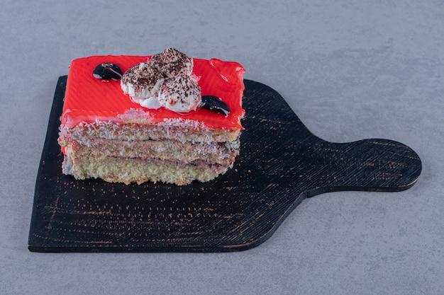 Délicieux gâteau aux fraises fait maison sur une planche à découper en bois noir