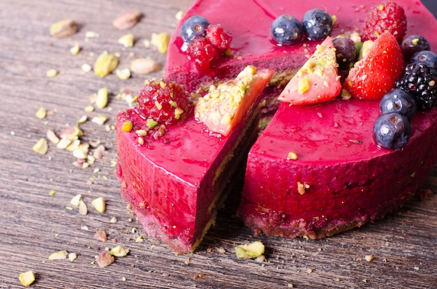 Délicieux gâteau aux framboises avec fraises fraîches, framboises, myrtilles, cassis et pistaches