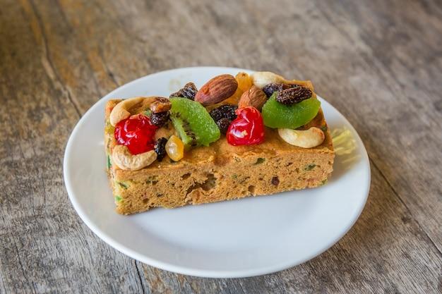 Délicieux gâteau aux fruits secs avec amandes et noix de cajou sur une assiette blanche et une table en bois.