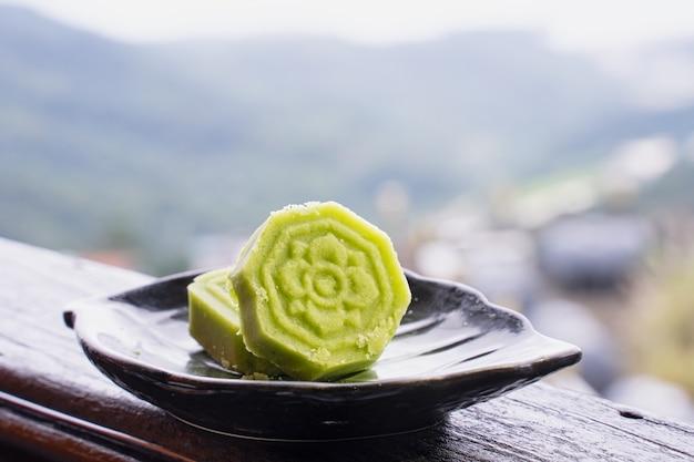 Délicieux gâteau aux haricots mungo vert avec plaque de thé noir sur balustrade en bois d'un salon de thé