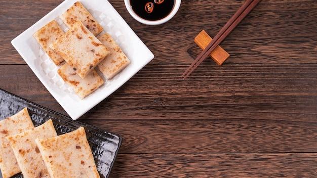 Délicieux gâteau aux navets, gâteau aux radis traditionnel chinois au restaurant avec sauce soja pour les plats du nouvel an, gros plan, espace de copie, vue de dessus, mise à plat.