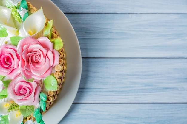 Délicieux gâteau aux roses, lis et feuilles sur une table en bois bleu clair