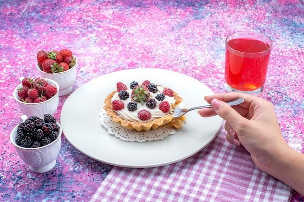 Délicieux gâteau crémeux se manger par femme avec différents jus de baies fraîches sur un bureau lumineux, couleur de fruits berry photo fraîche aigre