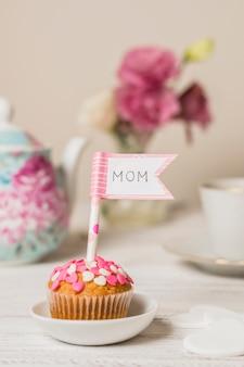 Délicieux gâteau avec drapeau décoratif avec titre de maman près de la théière et des fleurs