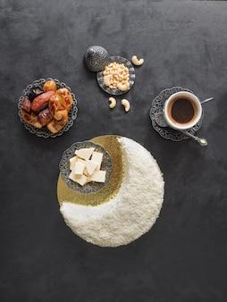 Délicieux gâteau fait maison en forme de croissant de lune, servi avec dattes et tasse de café