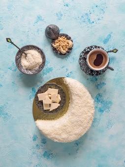 Délicieux gâteau fait maison en forme de croissant de lune, servi avec du chocolat blanc et une tasse de café