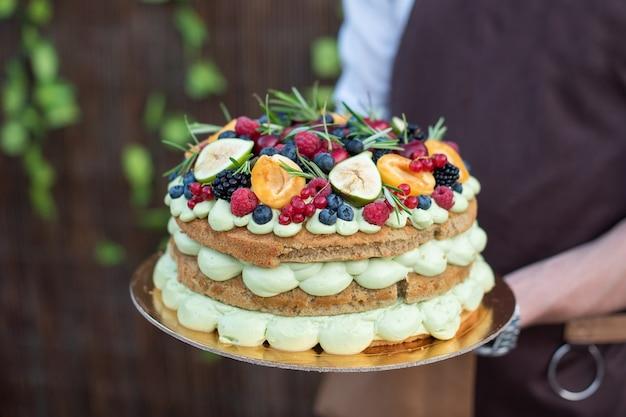 Délicieux gâteau fait maison recouvert de différents fruits entre les mains du boulanger