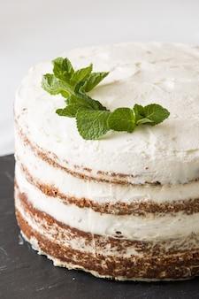 Délicieux gâteau nu fait maison avec glaçage à la crème blanche et feuilles de menthe servi sur tableau noir