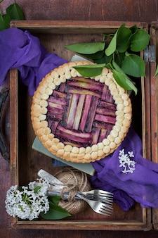 Délicieux gâteau à la rhubarbe fait maison avec des myrtilles sur un fond sombre
